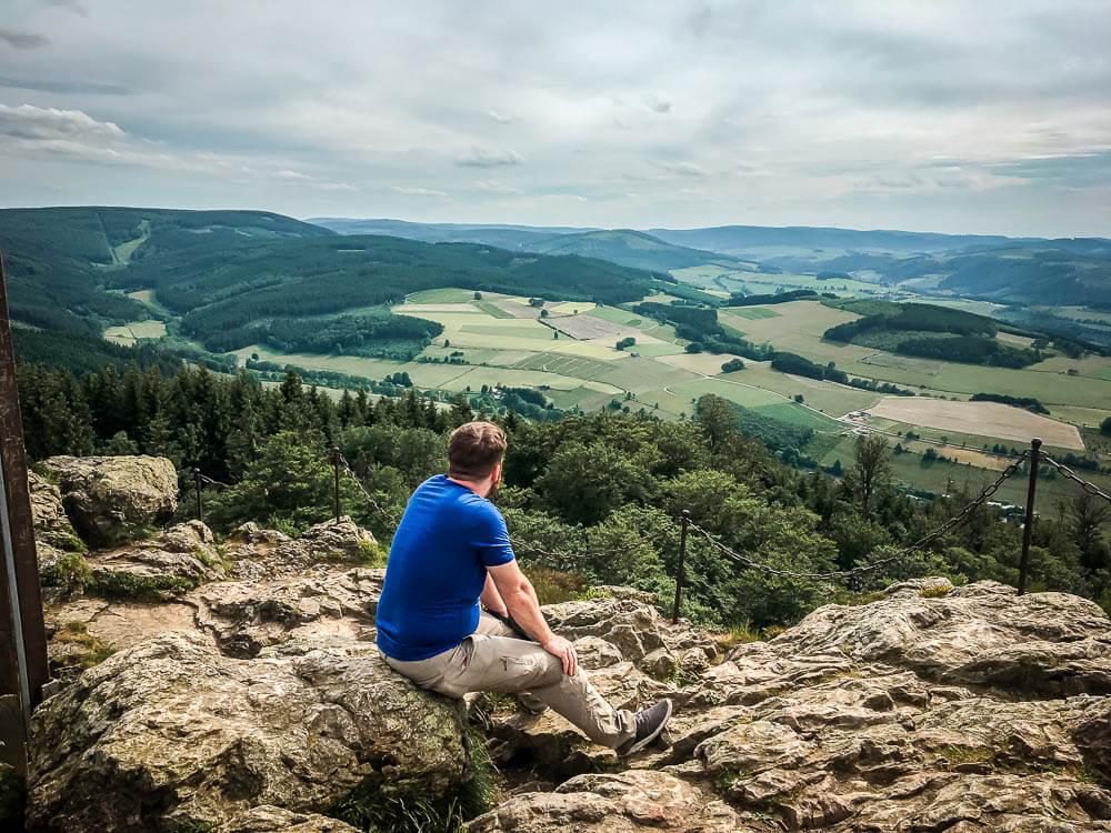 Mann genießt Aussicht auf die Landschaft im Sauerland von den Bruchhauser Steinen