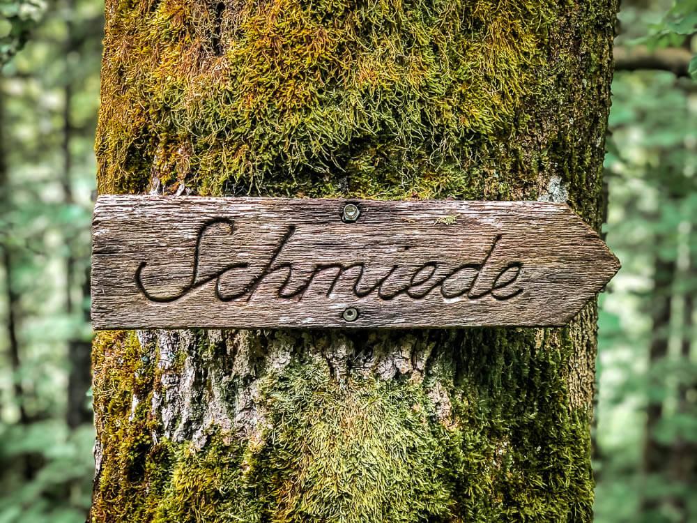Holzschild am Baum als Wegweiser zur Kunstschmiede in Niedersorpe