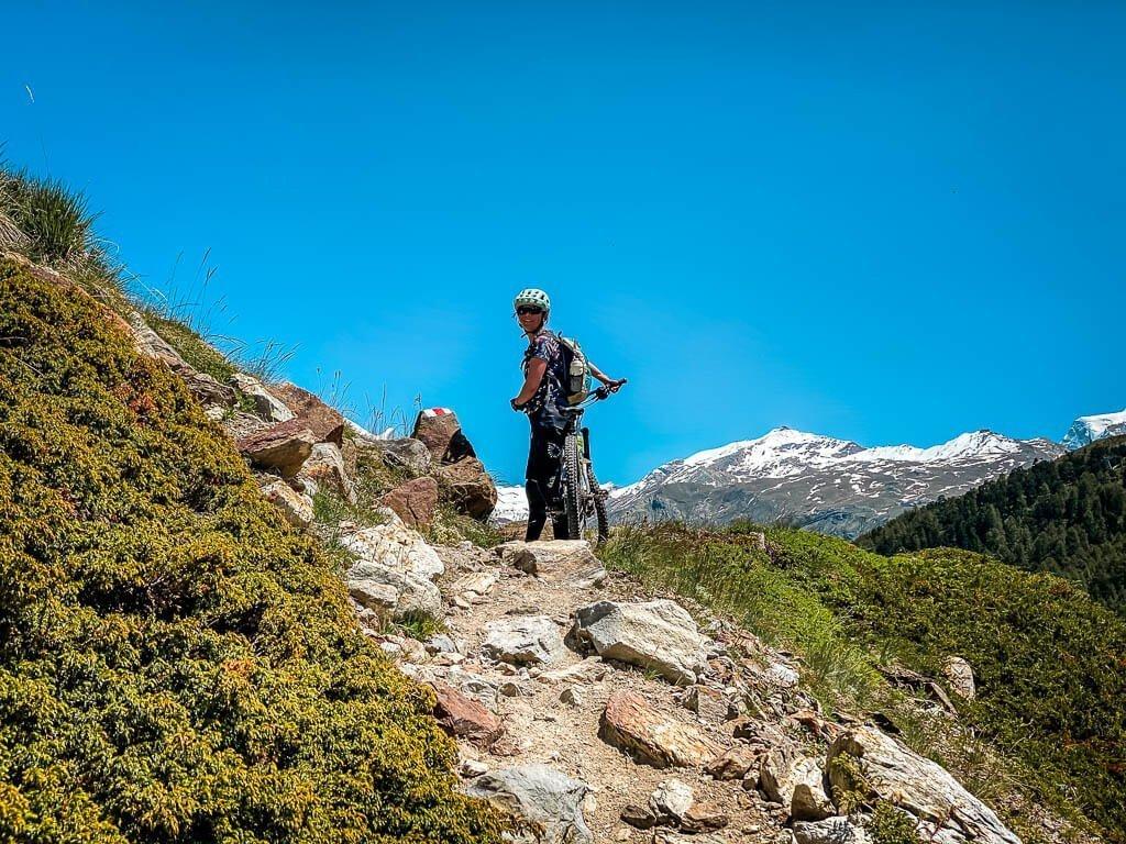 Zermatt Biken - Couchflucht Sabrina Bechtold mit Mountainbike auf einem felsigen Trail