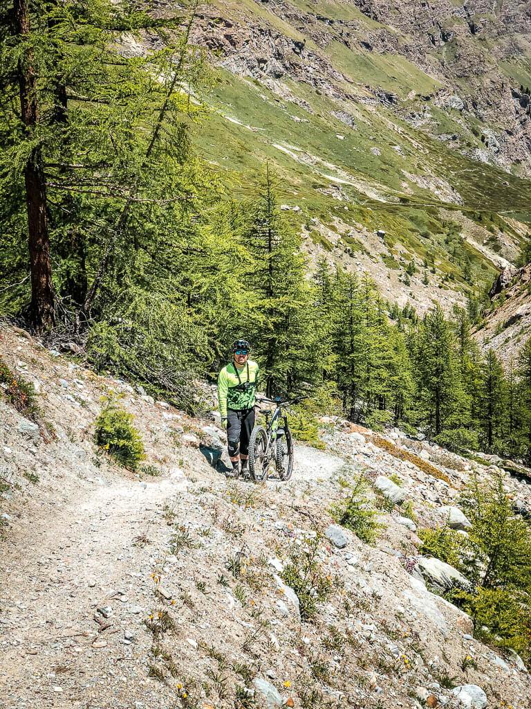 Zermatt Biken Mountainbiker schiebt sein Rad bergauf auf der Kalbermatten Tour