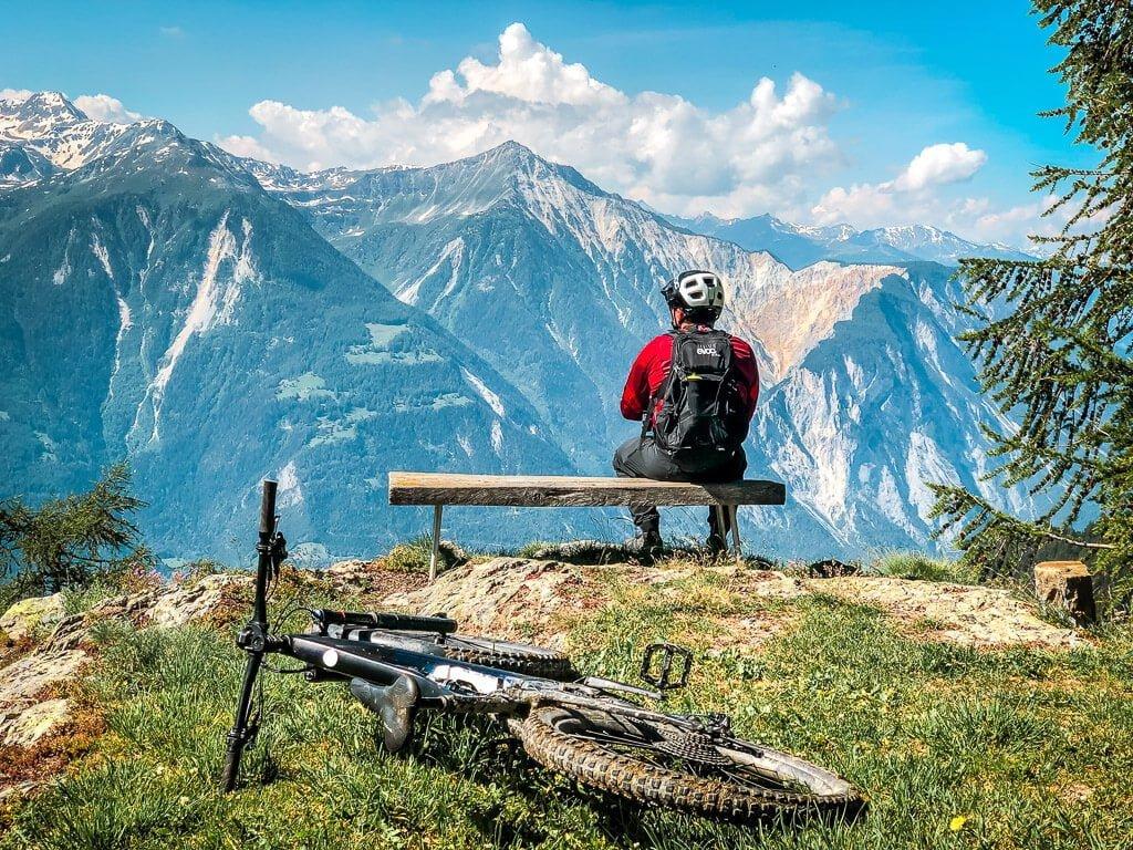 Leukerbad BIken - Mountainbiker macht Pause und genießt den Panoramablick auf die Walliser Alpen