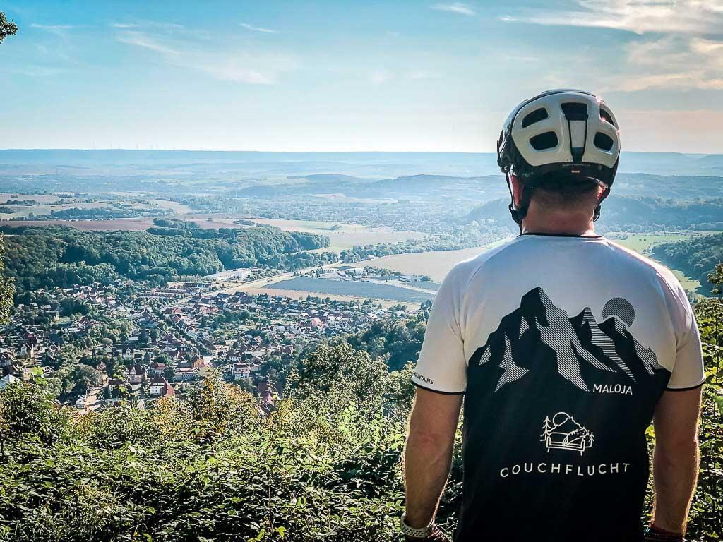Couchflucht Mountainbiker genießt die Aussicht an der Wetterfahne bei Ilfeld.