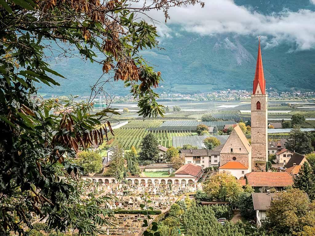Ausblick auf Kirche, Weinberge und Obstplantagen auf dem Marlinger Waalweg