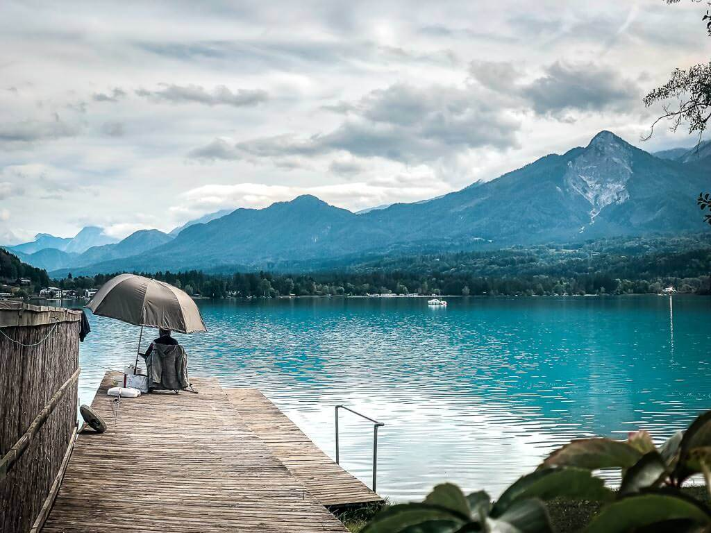Angler auf Steg am Faaker See in Kärnten