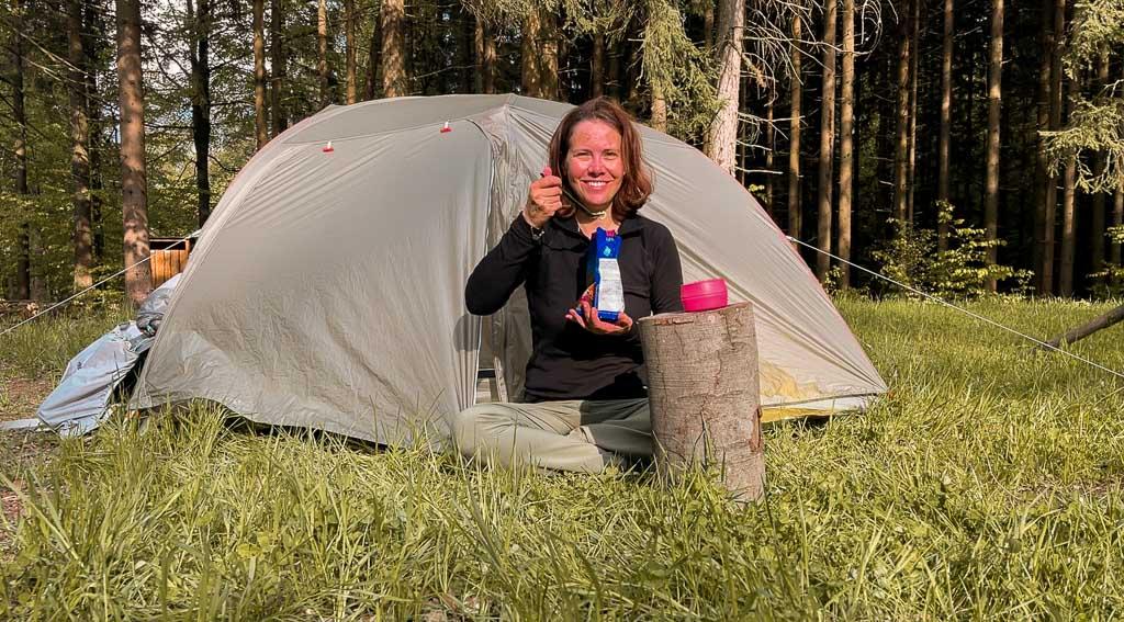 Couchflucht Sabrina Bechtold isst Trekkingessen vor dem Zelt auf dem Trekkingplatz Rehwiese im Frankenwald.